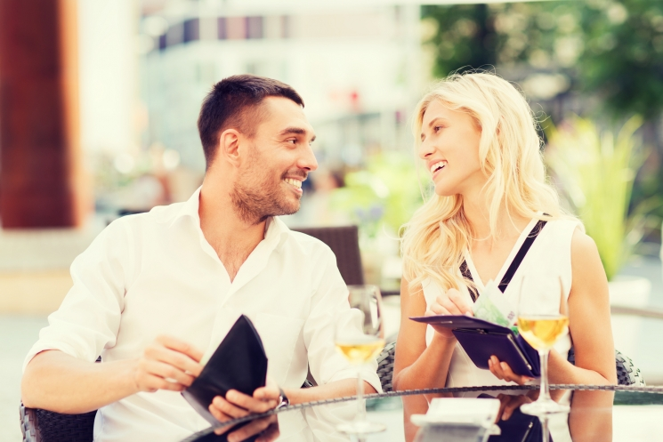 date, people, payment and financial independence concept - happy couple with cash money in wallets and wine glasses paying bill at restaurant