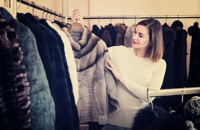 Young woman deciding on short coffee-colored fur jacket in women's cloths store