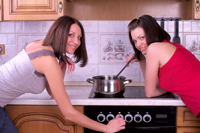 Two beautiful female trying to cook something on the home kitchen