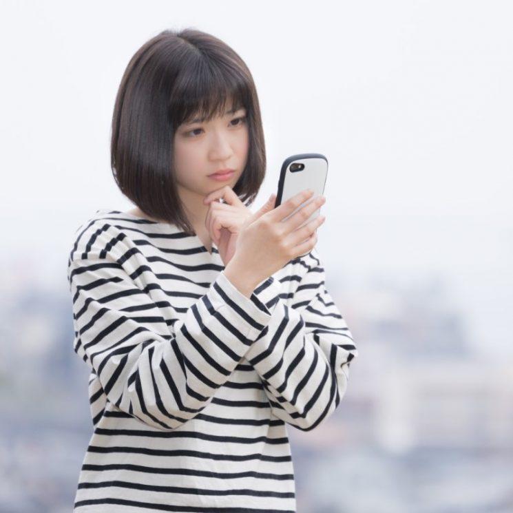 形態電話を見て悩む女性