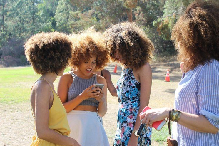 携帯電話を友達に見せる女の子