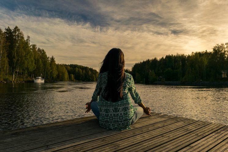 湖を見ながら瞑想するロングヘアーの女性