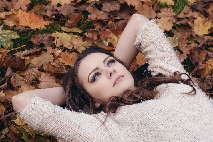 落ち葉の上に寝転び上を見つめる女性の写真