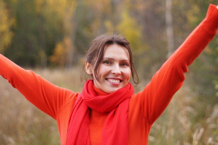 赤い服をきて両手をあげる女性の写真