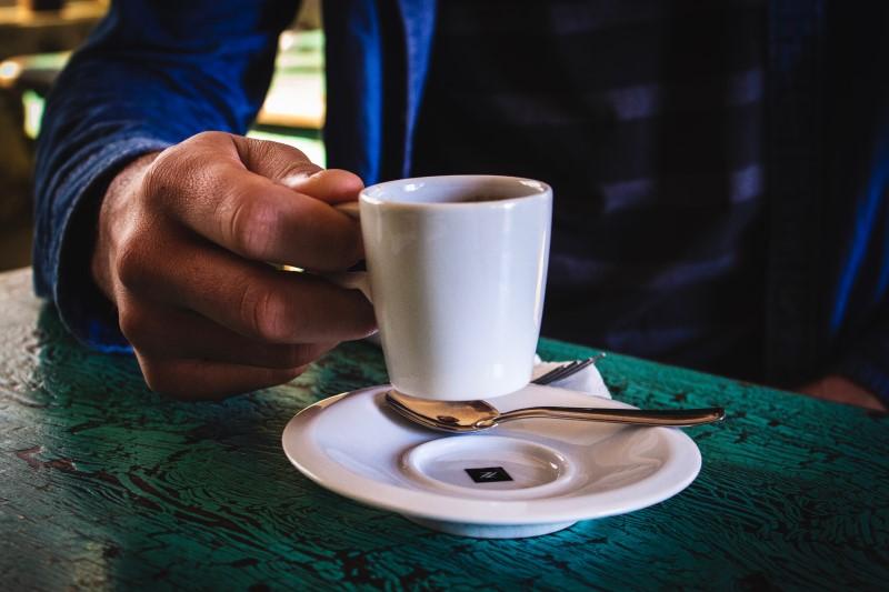 コーヒーカップを持ち上げる男性