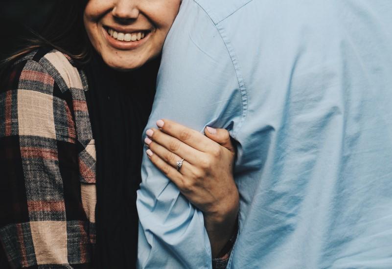 女性が男性の腕をつかみ微笑むイメージ