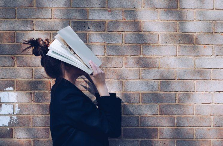 顔を本で覆う女性
